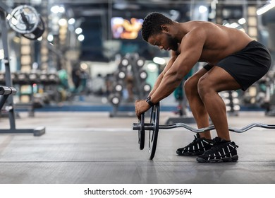 Powerlifting concept. Side view of black muscular shirtless man pumping iron in gym. Athletic african american guy bodybuilder building up muscles with barbell, hanging weight plate, copy space