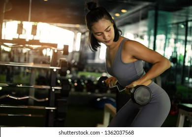 powerlifting and people sporty woman exercising with barbell in gym. exercise sport woman in fitness. low light and selective eye focus.
