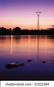 Powerline near the river against sunset
