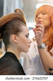 POZNAN - APRIL 18: Hairdresser arranging hairdo at The Look Beauty Vision Poznan 2015 on April 18, 2015 in Poznan, Poland.