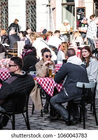 Poznan, Old town, Poland, 2 April 2018,  People with fashion cloths sitting and enjoy of good weather in the restaurant outdoor at the town, drinking beer.