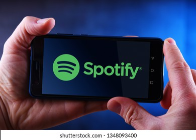 POZNAN, POL - MAR 24, 2019: Hands holding smartphone displaying logo of Spotify, a Swedish audio streaming platform that provides music and podcasts from record labels and media companies