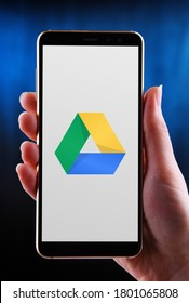 POZNAN, POL - MAY 21, 2020: Hands holding smartphone displaying logo of Google Drive, a file storage and synchronization service developed by Google