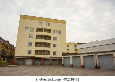 POZNAN, POLAND - APRIL 07, 2016: Row of garages with a apartment block at the end on a cloudy day