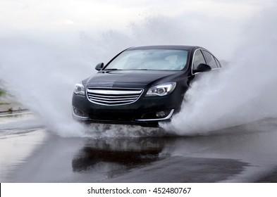 Poznan, Poland - April, 13, 2014: Modern car riding through the deep puddle.