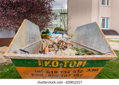 POZNAN, POLAND - APRIL 13, 2017: Metal Eko Tom waste container full of pieces close by apartment buildings