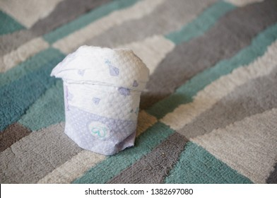 Poznan, Poland - April 13, 2019: Folded full Biedronka Dada baby diaper laying on a carpet floor.