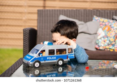 Poznan, Poland - April 15, 2018: Playmobil police van on a glass table with boy in soft focus background playing with it