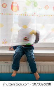 Poznan, Poland - April 16, 2018: Boy sitting by a window behind curtains in a room