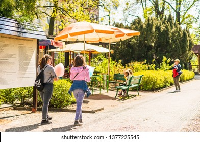 Poznan, Poland - April 18, 2019: Two girls with candyfloss walking on a footpath next to umbrellas in the old zoo on a warm spring season.