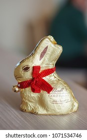 Poznan, Poland - April 2, 2018: Lindt golden milk chocolate bunny with red collar and a bell on wooden table. Traditional chocolate on Easter holidays.