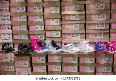 Poznan, Poland - April 20, 2018: Row of shoes in front of stacked boxes with different sizes for sale in a CCC store