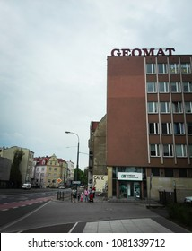 Poznan, Poland - April 23, 2018: People walking on a sidewalk next to a building with Geomat office and Credit Agricole bank