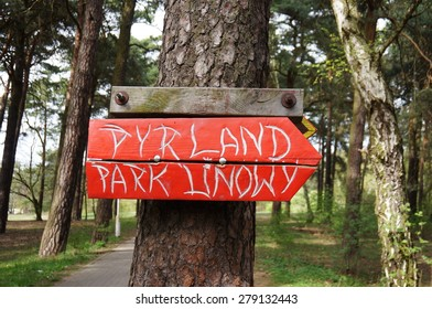 POZNAN, POLAND - APRIL 25, 2015: Red wooden sign on tree showing direction to a climbing park