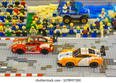 Poznan, Poland - April 28, 2018: Two Lego racing cars with a audience watching ready for the start in soft focus