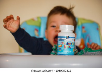 Poznan, Poland - April 28, 2018: Nordic Naturals Children's DHA cod liver pills in a container with baby in soft focus background