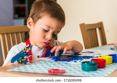 Poznan, Poland - April 28, 2020: Young boy finger painting with blue color.