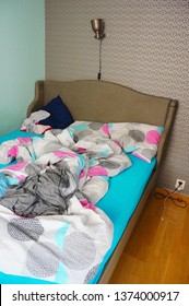 Poznan, Poland - April 9, 2019: Messy bed in a bedroom with lamp and wallpaper.