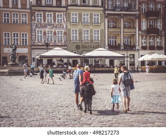POZNAN, POLAND - AUGUST 11, 2013: Young girl riding a pony on the old city square