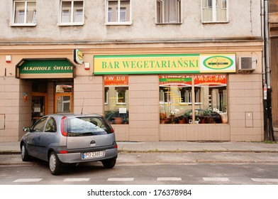 POZNAN, POLAND - AUGUST 18, 2013: Parked car in front of a vegetarian restaurant