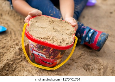 Poznan, Poland - August 25, 2018: Child holding a red plastic toy bucket filled with sand in a sandpit. It has illustration of Lightning McQueen from the Pixar Disney Cars movie.