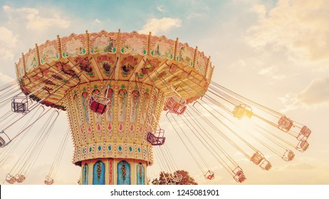 Poznan, Poland - August 27, 2017: Carousel ride spins fast in the air at sunset at Malta Lake in Poznan
