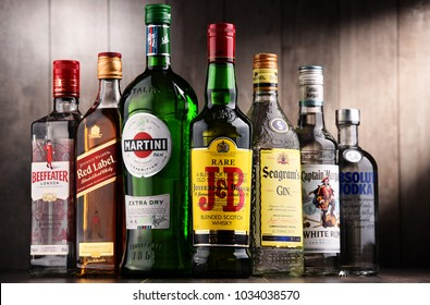 POZNAN, POLAND - DEC 15, 2017: Bottles of assorted global liquor brands including Martini, Johnnie Walker, Captain Morgan, Absolut Vodka, Beefeater and JB