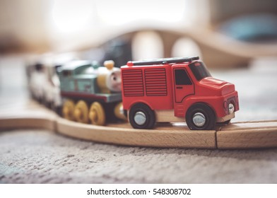 POZNAN, POLAND - DECEMBER 02, 2016: Small wooden toy fire department truck including Thomas and Friends locomotive on a track on a floor in soft focus
