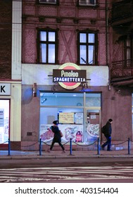 POZNAN, POLAND - DECEMBER 05, 2013: People passing a Pinokio Spaghetteria in the city center by night