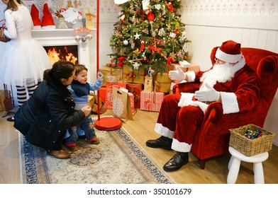 POZNAN, POLAND - DECEMBER 06, 2015: Mother and two years old boy by sitting Santa Claus in the Galeria Malta shopping mall