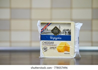 POZNAN, POLAND - DECEMBER 18, 2017: Polish Smaki Swiata British cheddar cheese packed with 10 slices on a wooden table