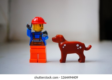 Poznan, Poland - December 22, 2018: Lego construction worker standing next to his best dog friend in soft focus background.
