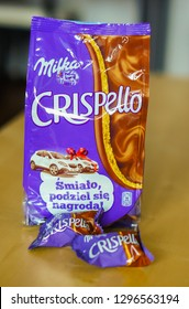 Poznan, Poland - December 8, 2013: Milka Crispello chocolate snack in a bag standing on a wooden table in soft focus.