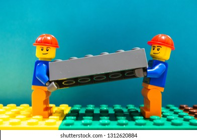 Poznan, Poland - February 13, 2019: Two Lego construction workers with helmet lifting together as a team a gray plastic brick. Teamwork is very helpful during work.