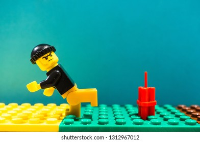 Poznan, Poland - February 13, 2019: Lego man with hat running away from dynamite ready to explode soon. Man is fleeing creating a act of terrorism.