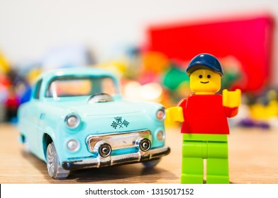 Poznan, Poland - February 15, 2019: Lego man figurine standing next to his parked old time car. Proud owner of his vintage vehicle.