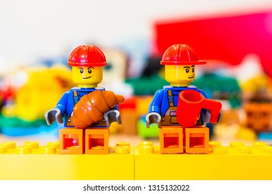 Poznan, Poland - February 15, 2019: Lego toy construction workers with safety helmet having a break while sitting on yellow blocks eating a croissant and drinking coffee during work time.