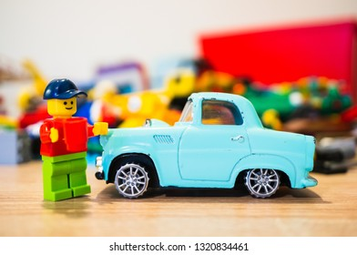 Poznan, Poland - February 15, 2019: Lego man with hat standing next to his classic parked car. He is the proud owner.