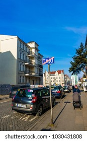 Poznan, Poland - February 20, 2018: Row of parked taxis by a sidewalk in the city