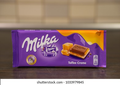 Poznan, Poland - February 25, 2018: Milka Toffee Creme chocolate on a wooden table