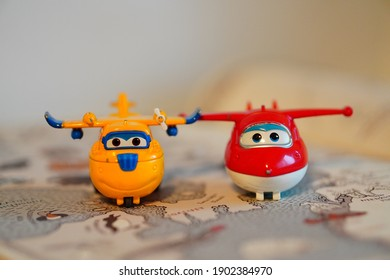POZNAN, POLAND - Jan 24, 2021: Jett and Donnie Super Wings action figures on a opened book with map in soft focus background