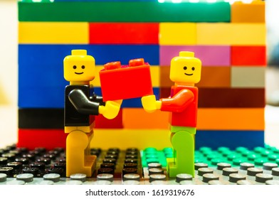 Poznan, Poland - January 18, 2020: Two smiling Lego figurines carrying together a red brick in front of a colorful wall.