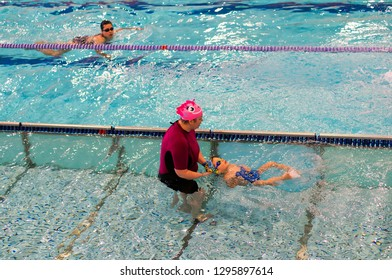 Poznan, Poland - January 26, 2019: Woman assisting boy swimming on his back in a pool during swim lessons in the Termy Maltanskie.