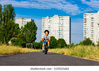 Poznan, Poland - July 10, 2018: Young boy on a small bicycle with safety helmet on a path with apartment blocks in the background