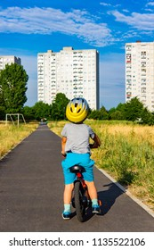 Poznan, Poland - July 10, 2018: Young boy with safety helmet sitting on a bicycle while looking at apartment blocks