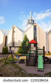 Poznan, Poland - July 10, 2018: Playground equipment with swinging boy in front of a church on the Stare Zegrze district