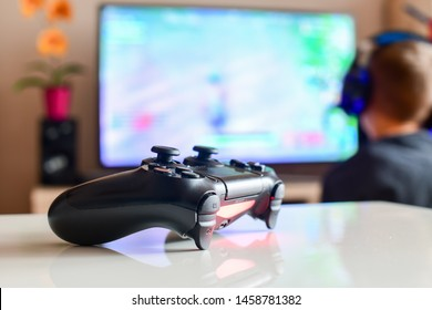 Poznan, Poland, July 23, 2019: Playstation 4 controller, which is turned on, in front of a blurred television showing the Playstation home screen.