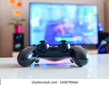 Poznan, Poland, July 23, 2019: Playstation 4 controller. Video game controller in front of blurred TV background - Gaming concept