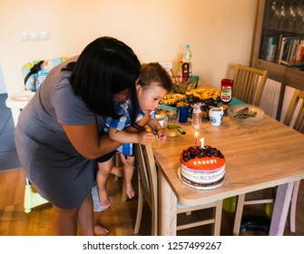 Poznan, Poland - July 28, 2018: Woman helping toddler boy blowing a candle on a cake during his first birthday in a Polish home.