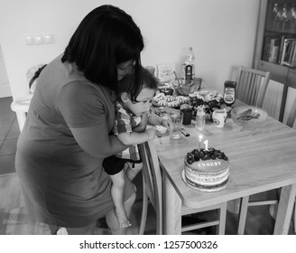 Poznan, Poland - July 28, 2018: Woman helping toddler boy blowing a candle on a cake during his first birthday in a Polish home in black and white.
